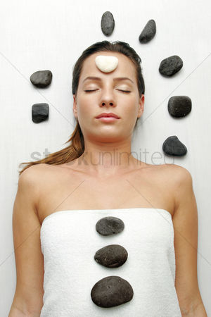 Satisfying : A sleeping lady with a white stone on her forehead and black stones on her body and around her head
