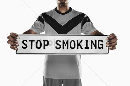 Match : A soccer player holding  stop smoking  sign