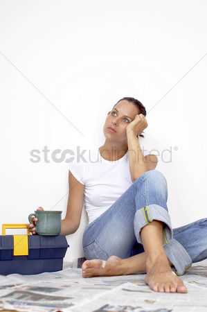 Wondering : A woman in jeans sitting on a newspaper covered floor