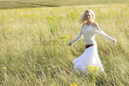 Enjoying : A woman running happily on the prairie