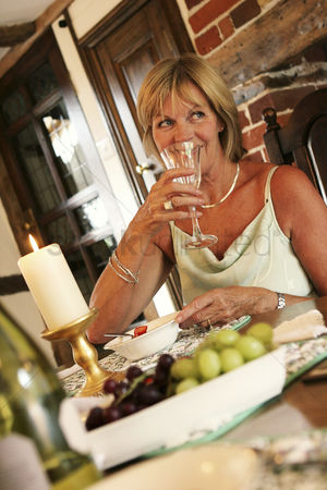 Grapes : A woman sitting at the dining table drinking a glass of wine
