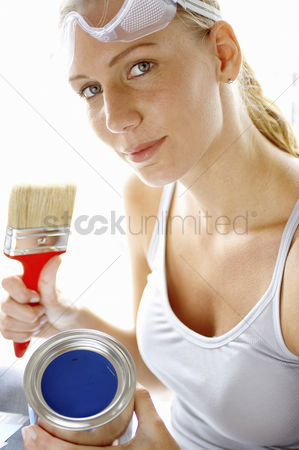 Goggle : A woman with goggles holding a brush and a tin of blue paint