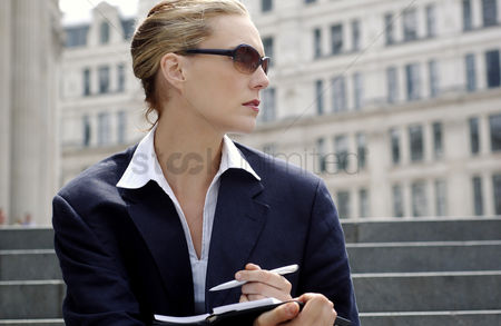Outdoor : A woman with sunglass sitting on the stairs writing notes on her organizer