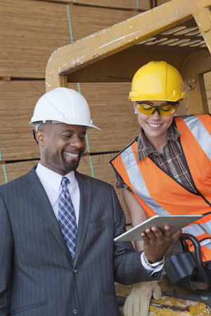 Forklift : African american businessman and female industrial worker looking at tablet pc