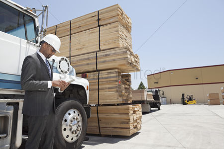 Land : African american male contractor using tablet pc while standing by logging truck