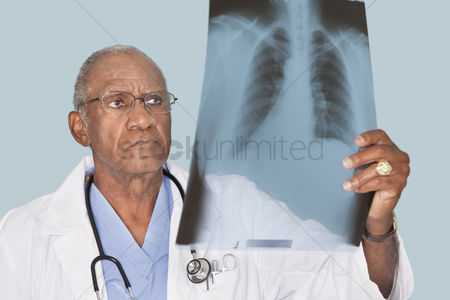 Head shot : African american male doctor analyzing x-ray report over light blue background