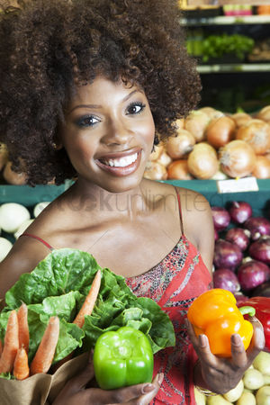 Supermarket : African american woman holding bell peppers and vegetables at supermarket