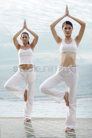 Practising yoga : An asian and a woman practising yoga technique