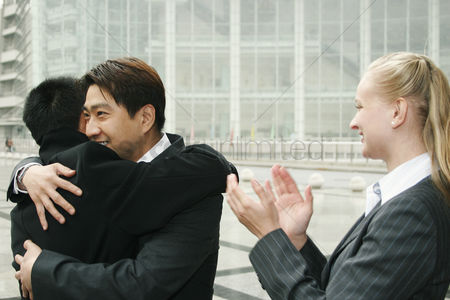 Client : An asian man hugging his friend while a lady clapping her hands