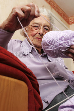 Bespectacled : An old bespectacled lady sitting on the couch pulling her knitting thread