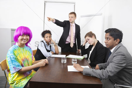 Instruction : Angry multiethnic businesspeople with colleague in pink wig at meeting