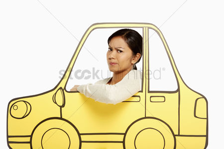Frowning : Annoyed woman looking out of a cardboard car window