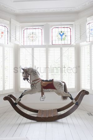 Window : Antique rocking horse in bay window with stained glass london