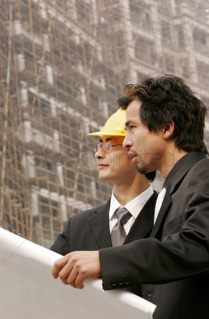 Bespectacled : Architect discussing a building plan with his client at a construction site