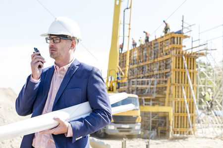 Supervisor : Architect using walkie-talkie while holding blueprints at construction site