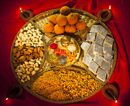 Almond : Assorted diwali sweets and snacks with diwali diyas