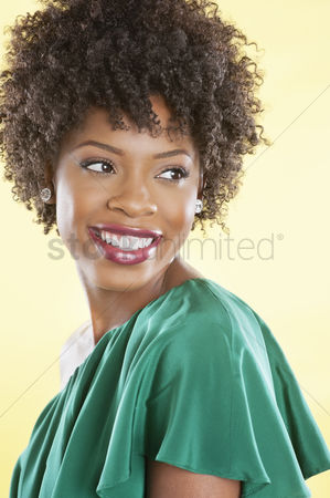 Elegance : Attractive african american woman in an off shoulder dress looking away over colored background