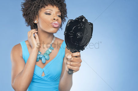 Curly hair : Attractive african american woman puckering while looking in mirror over colored background