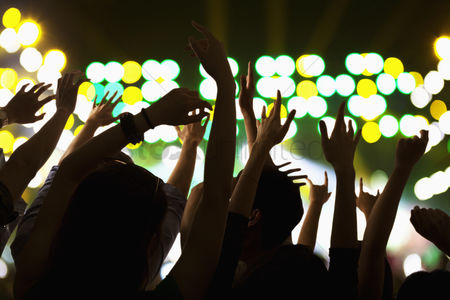 Dancing : Audience watching a rock show  hands in the air  rear view  stage lights