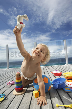 Toy : Baby boy playing on porch with lots of toys