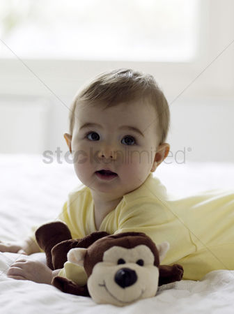 Adorable : Baby girl lying forward on the bed with her toys