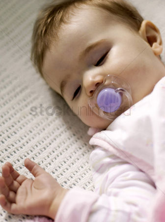 Comfort : Baby girl with pacifier sleeping in the crib