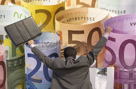 Celebrating : Back view of victorious businessman with briefcase against rolled up euros