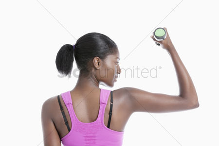 Sports : Back view of young woman raising dumbbell over white background