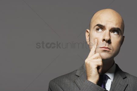 Contemplation : Bald businessman with hand on chin thinking