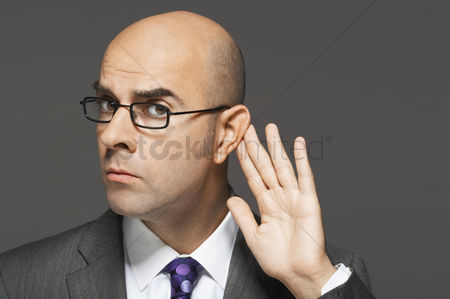 Business suit : Balding man with hand behind ear listening closely