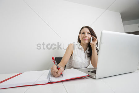 Businesswomen : Beautiful businesswoman answering cell phone while writing at desk in office