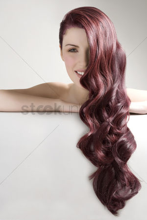 Smiling : Beautiful woman with long red dyed hair against gray background