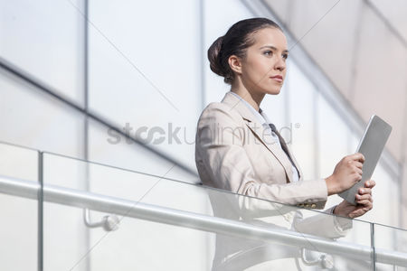 Employee : Beautiful young businesswoman holding digital tablet at office railing