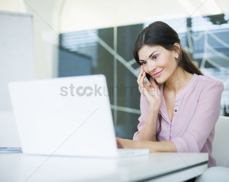 Czech republic : Beautiful young businesswoman using mobile phone while looking at laptop in office