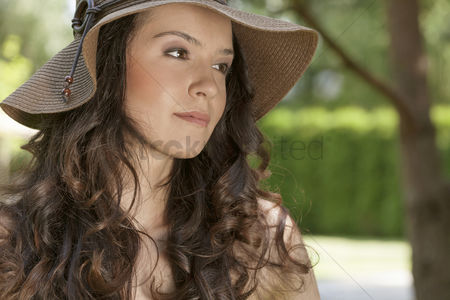 Beautiful people : Beautiful young woman in sunhat looking away in park