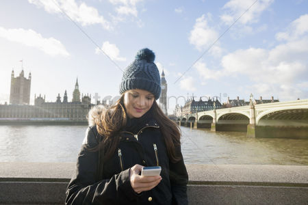 England : Beautiful young woman reading text message through smart phone by river thames  london  uk
