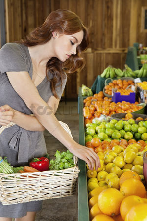 Supermarket : Beautiful young woman selecting fruit in market