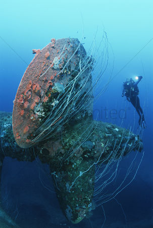 Diving : Bikini atoll marshall islands pacific ocean scuba diver swimming near propeller of sunken battleship hijms nagato