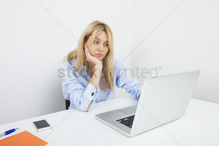 Office worker : Bored young businesswoman using laptop at desk in office