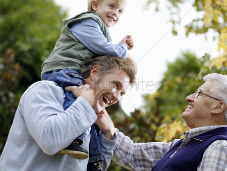 Appearance : Boy  3-4  riding on father s shoulders grandfather looking on in yard low-angle view