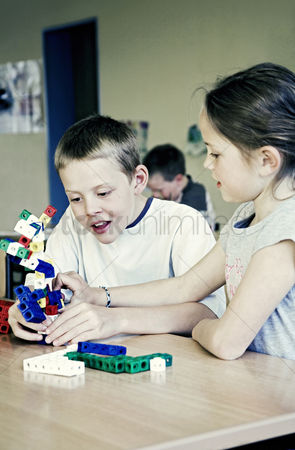 Children playing : Boy and girl assembling plastic blocks