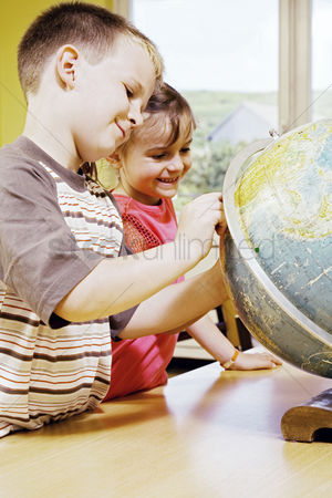 Young boy : Boy and girl referring to a globe