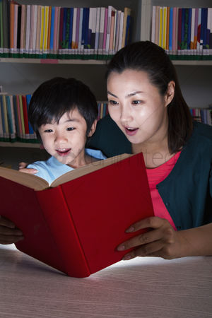 Amazed : Boy and teacher surprised by glowing book