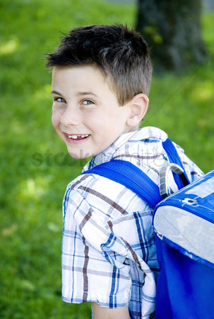 School children : Boy carrying school bag on his back