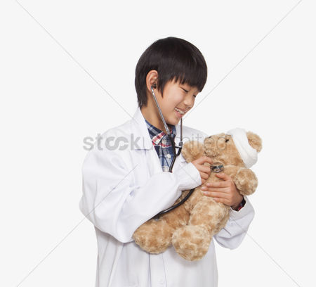 Having fun : Boy dressed up as doctor checking teddy bear s vital signs