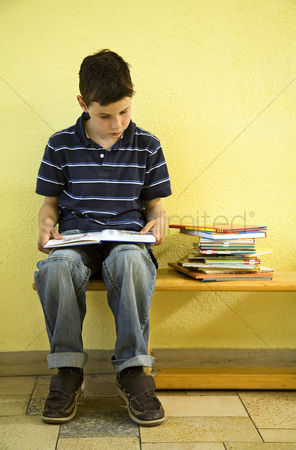 School children : Boy sitting on the bench reading book
