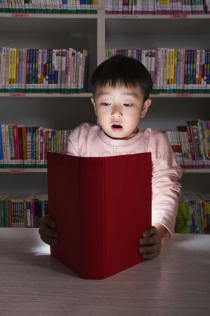 Amazed : Boy surprised by glowing book