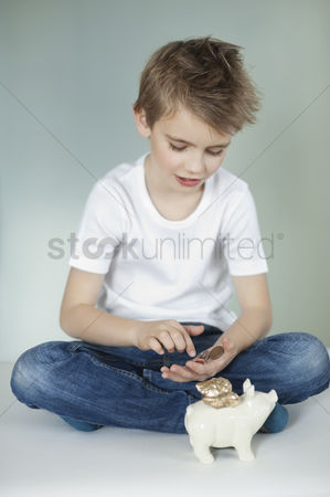 Denim : Boy with piggy bank counting coins over gray background