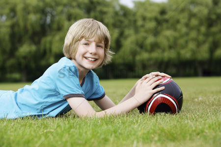 Spring : Boy with soccer ball lying forward on the field