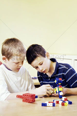Children playing : Boys assembling plastic blocks